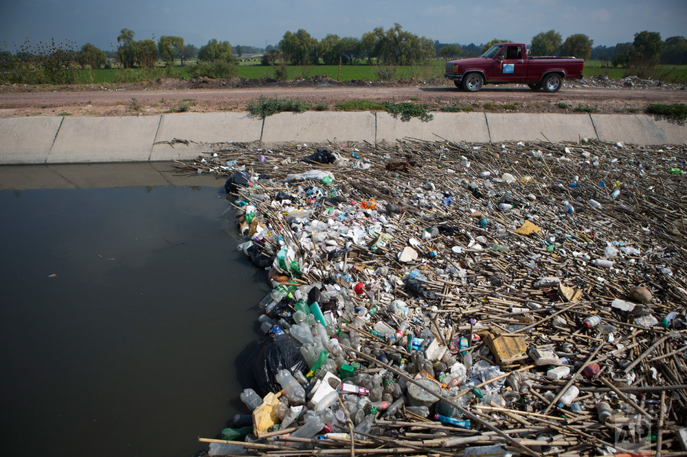 In this March 16, 2017 photo, refuse piles up behind a flow control gate in a principal wastewater irrigation canal near Mixquiahuala, Hidalgo state, Mexico. When the much-delayed plant is up and running, the portion of the metropolis' 20 million-plus people's sewage that gets treated will rise to 57 percent, compared with 11 percent when construction began in 2010. (AP Photo/Rebecca Blackwell)
