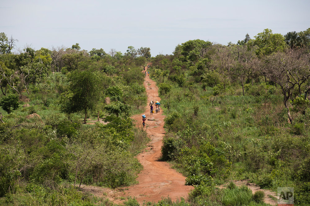 In this Wednesday March 29, 2017 photo, South Sudanese refugees walk towards the Ugandan border at Busia. There were high hopes that South Sudan would have peace and stability after its independence from neighboring Sudan in 2011. But the country plunged into ethnic violence in December 2013 when forces loyal to President Salva Kiir, a Dinka, started battling those loyal to Riek Machar, his former vice president who is a Nuer. (AP Photo/Jerome Delay)