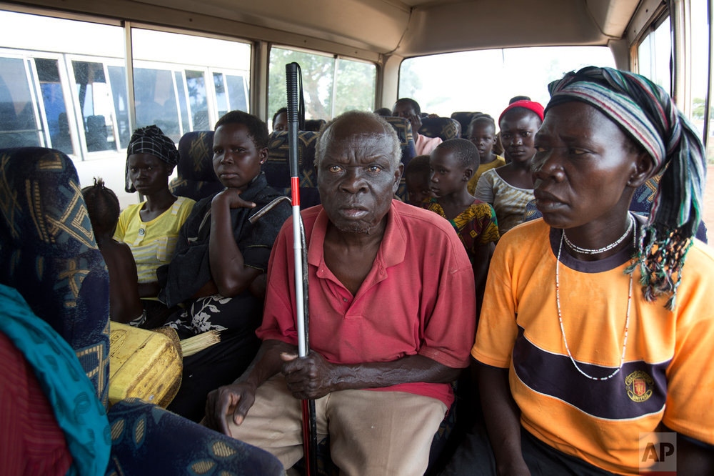 In this Wednesday March 29, 2017 photo, Jenifer Juan, daughter of Alfred Wani, sits next to Ringo Gwiya, center, in a minibus after being processed by U.N. officials in Busia, Uganda. They were later transported to the Kuluba transit camp. (AP Photo/Jerome Delay)