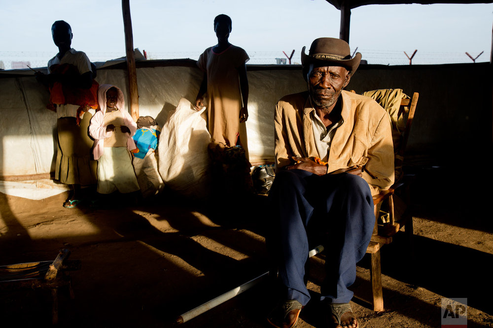 In this Friday March 31, 2017 photo, Alfred Wani sits in a communal tent at the Kuluba, Uganda, transit camp, waiting for transport to Imvepi camp. Alfred is one of more than 800,000 South Sudanese who have fled to Uganda just since July. (AP Photo/Jerome Delay)