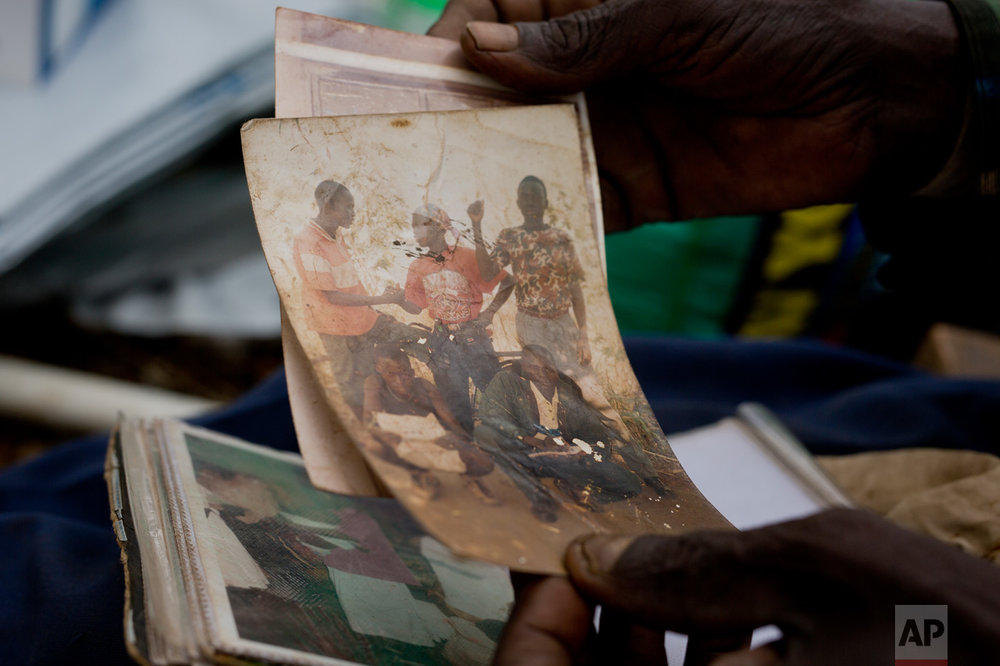 In this Tuesday, April 4, 2017 photo, Alfred Wani holds a faded photograph of some of his sons. Wani, 80, fled South Sudan's civil war and crossed into Uganda with his bibles, a family photo album, his wife Kassa, three goats and 27 relatives. (AP Photo/Jerome Delay)