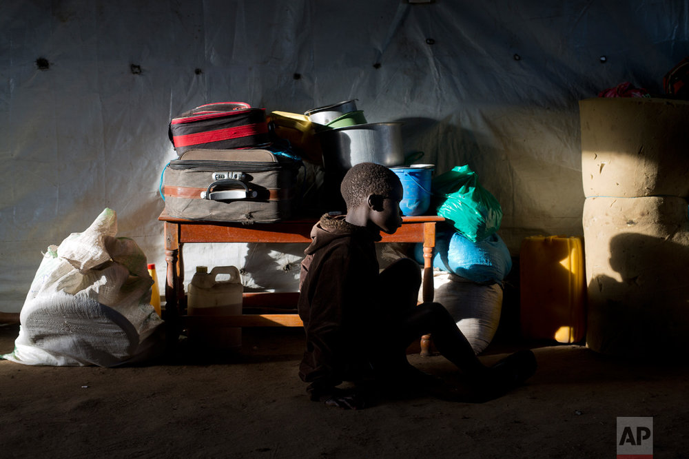 In this Friday March 31, 2017 photo, Daniel Kampa, 8, sits in a ray of light by his suitcase in a communal tent at the Kuluba, Uganda, transit camp, waiting for transport to the Imvepi camp. (AP Photo/Jerome Delay)