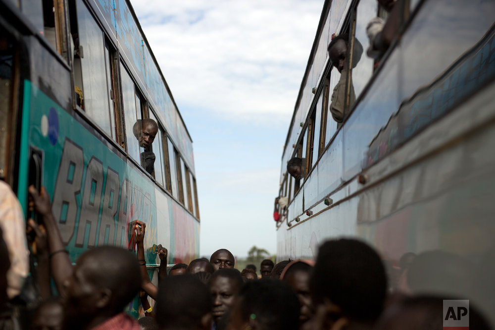 In this Friday March 31, 2017 photo, South Sudanese refugees board buses at the Kuluba transit camp in Uganda. Over 1000 refugees transit daily through here and are then transported to Imvepi for permanent settlement. (AP Photo/Jerome Delay)