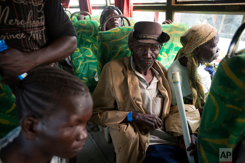 In this Friday March 31, 2017 photo, Alfred Wani and his wife, Kassa, sit in a bus at the Kuluba transit camp. Over 1,000 refugees transit daily through Kuluba and are then transported to Imvepi for permanent settlement. (AP Photo/Jerome Delay)
