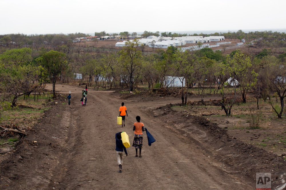In this Thursday, April 6, 2017 photo, South Sudanese children carry water jugs down a road in the new Imvepi refugee settlement in northern Uganda. In the background are the communal tents for the processing center. Imvepi is growing at a rate of over 2,000 refugees each day. (AP Photo/Jerome Delay)