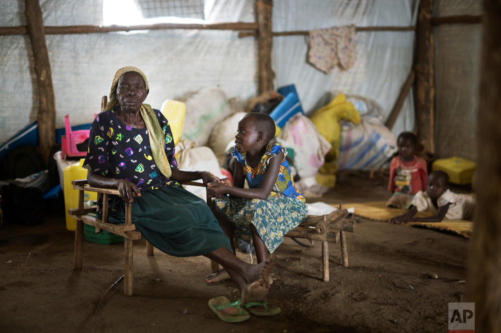 In this Monday, April 3, 2017 photo, Stella, 10, comforts her grandmother, Kassa, whose husband, Alfred, is in the camp's clinic waiting for blood results at the Imvepi refugee settlement in northern Uganda. Alfred's illness postponed the family's scheduled resettlement by a day. (AP Photo/Jerome Delay)
