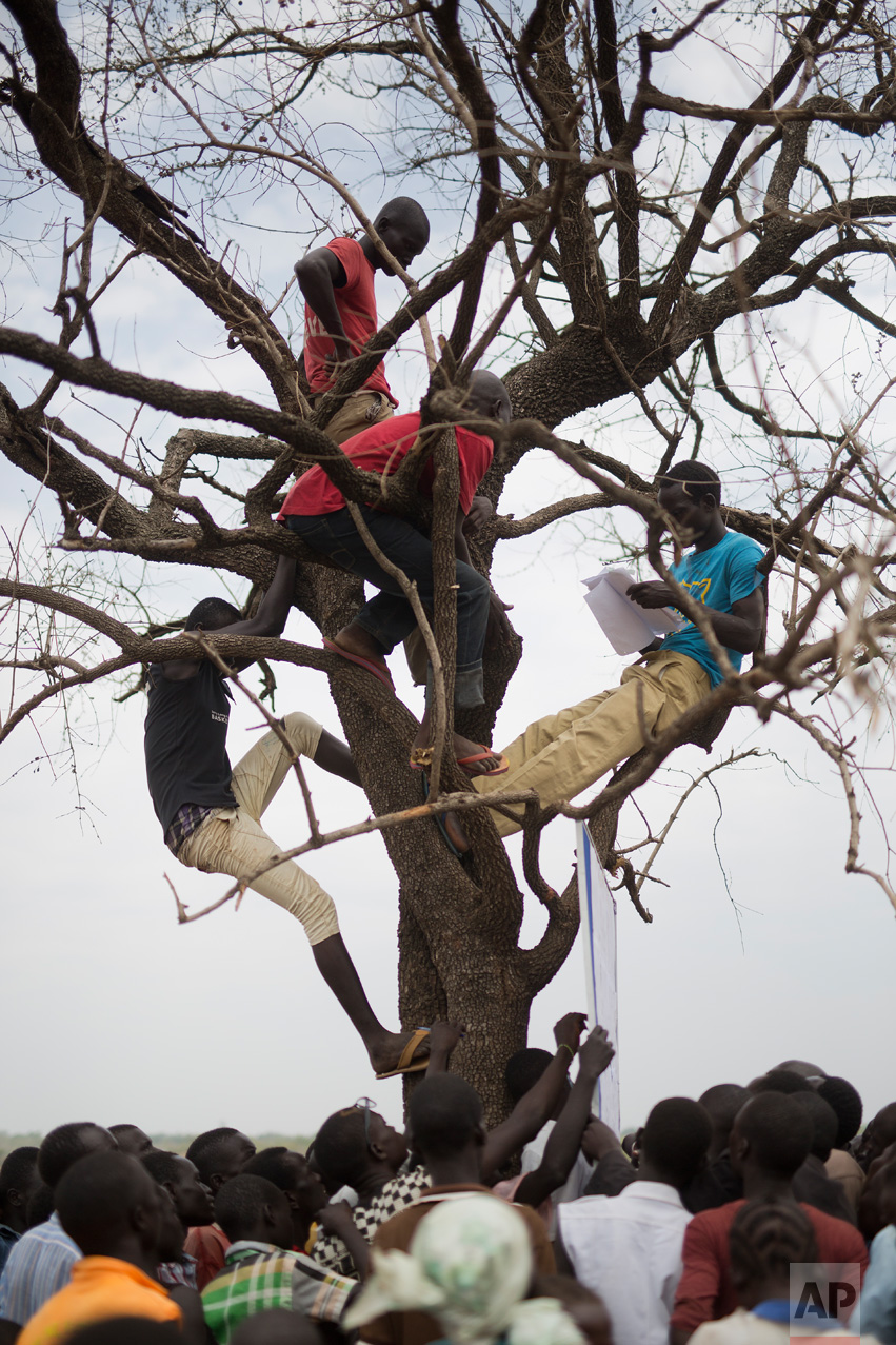 In this Monday, April 3, 2017 photo in the Imvepi camp, South Sudanese refugees gather under a tree from which names are announced for those allocated a land parcel from the Ugandan government. (AP Photo/Jerome Delay)