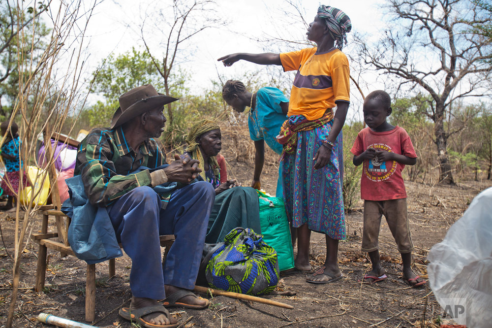 In this Tuesday, April 4, 2017 photo in the Imvepi camp, Jenifer Juan points at children as her parents, Alfred and Kassa Wani rest on chairs after traveling by truck to the plots of land they were allocated by the Ugandan government for their resettlement. Imvepi is growing at a rate of over 2,000 refugees each day. (AP Photo/Jerome Delay)