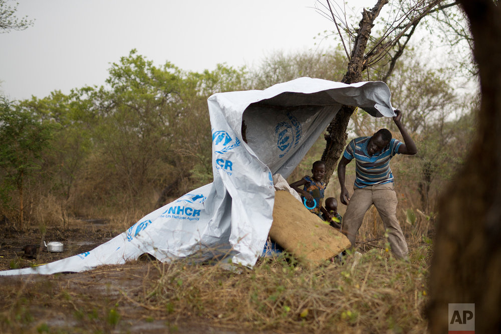 In this Wednesday, April 5, 2017 photo in the Imvepi camp, Samson Wani grabs a flapping plastic cover during a rain storm on the plot of land he and family were allocated by the Ugandan government for their resettlement. (AP Photo/Jerome Delay)