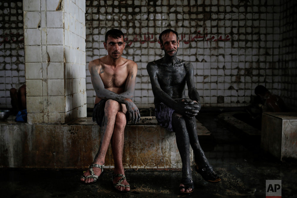 Two customers of the Hamam Alil spa south of Mosul, Iraq, take a break from bathing after covering themselves with mud from a nearby sulphur well, Thursday, April 27, 2017. The mud is supposedly healthy for the skin. (AP Photo/Bram Janssen)