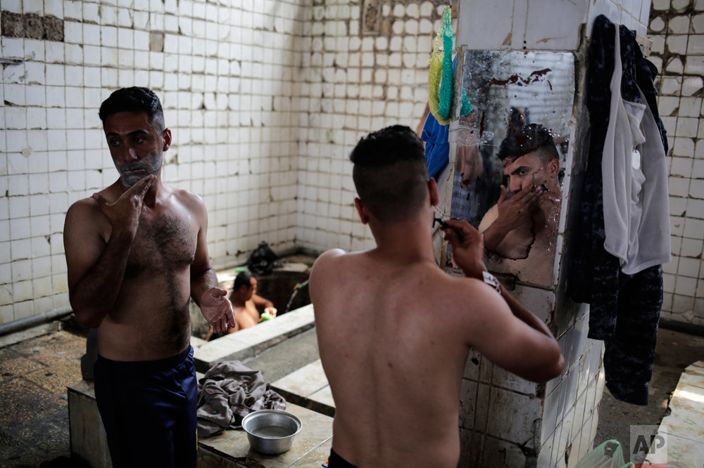 A customer shaves in front of a mirror in the Hamam Alil sulphur spa south of Mosul, Iraq, on Thursday, April 27, 2017. Many Iraqi soldiers visit the spa, located half an hour south of Mosul, in between fighting against the Islamic State group for relaxation. (AP Photo/Bram Janssen)