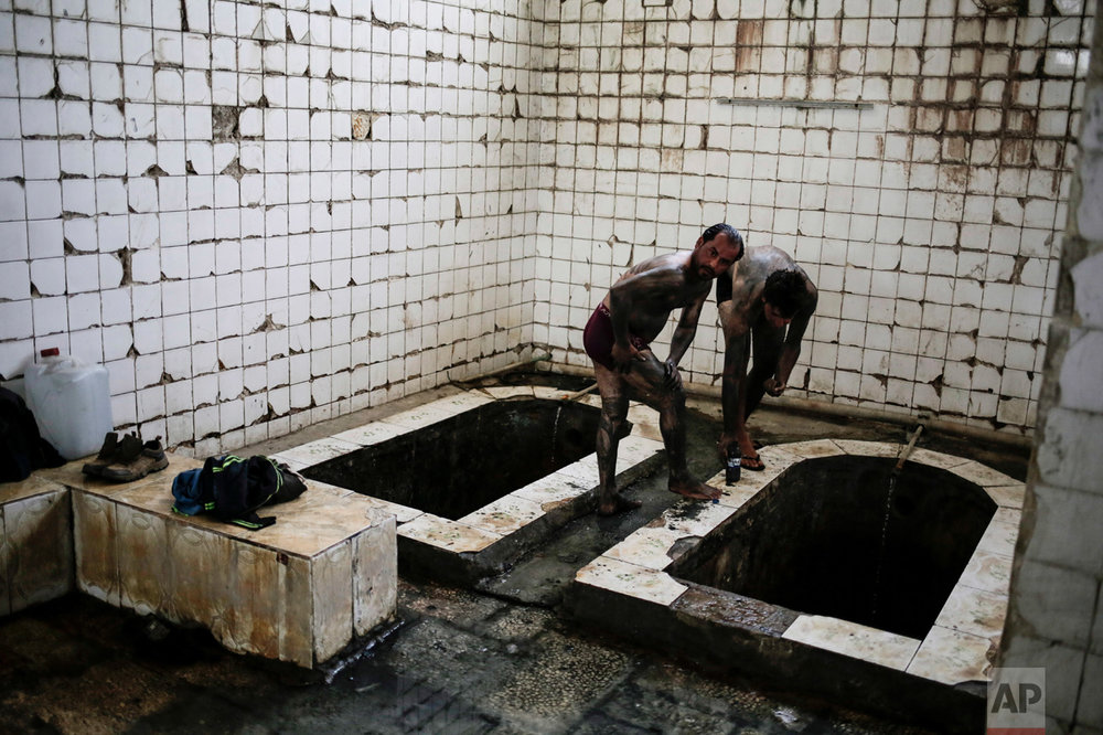 Customers cover themselves with mud from the sulphur well in Hamam Alil south of Mosul, Iraq, on Thursday, April 27, 2017. The mud is supposedly healthy for the skin. (AP Photo/Bram Janssen)