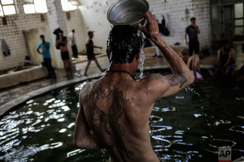 A customer pours water over himself in the Hamam Alil sulphur spa south of Mosul, Iraq, on Thursday, April 27, 2017. Many Iraqi soldiers go to the spa, located half an hour south of Mosul, in between fighting against the Islamic State group for relaxation. (AP Photo/Bram Janssen)