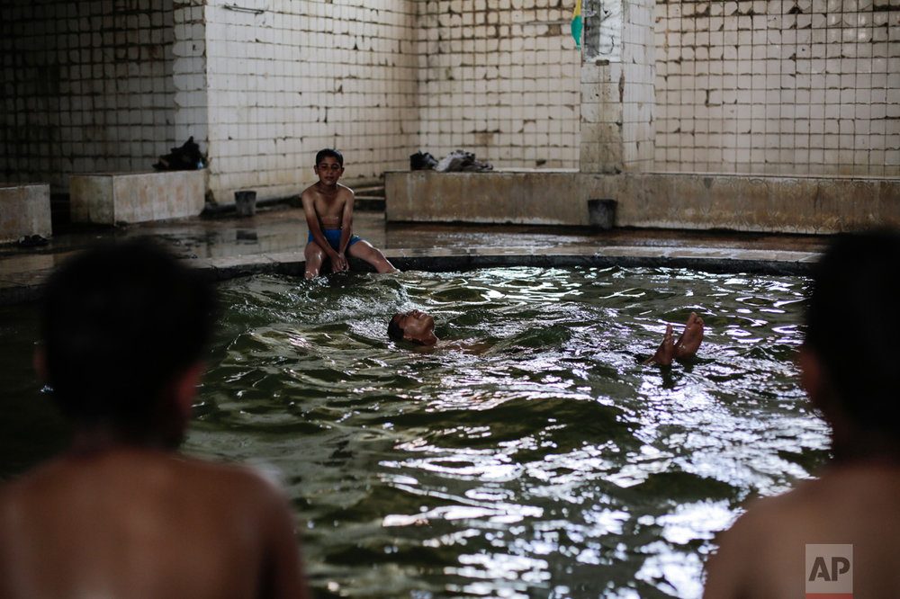 A boy swims in the pool filled with water from a sulphur well in the Hamam Alil sulphur spa on Thursday, April 27, 2017. Before the Islamic State took over the town of Hamam Alil in 2014, people from all over Iraq visited the historic spa south of Mosul. (AP Photo/Bram Janssen)