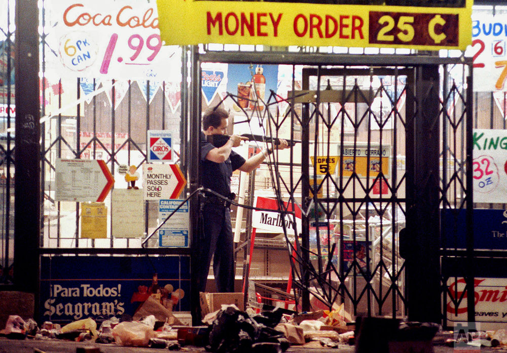 In this April 30, 1992 photo, a Los Angeles police officer takes aim at a looter in a market at Alvarado and Beverly Boulevard in Los Angeles during the second night of rioting in the city. (AP Photo/John Gaps III)