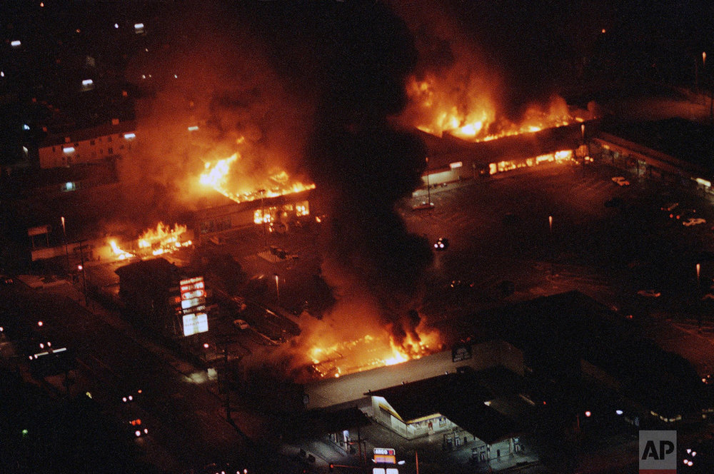 In this Wednesday, April 30, 1992 photo, several buildings in a shopping center are engulfed in flames before firefighters arrive as rioting continued in South-Central Los Angeles in the aftermath of the verdicts in the Rodney King assault case. (AP Photo/Reed Saxon)