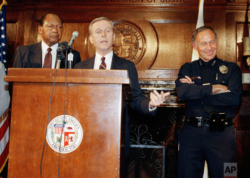 Governer Pete Wilson, center, saying at a press conference Thursday night in Los Angeles, May 1, 1992 that 2,000 National Guardsmen have been deployed with an additional 2,000 ready to be deployed. Wilson added that another 2,000 guardsmen could be called into the area as needed. Mayor Tom Bradley and Chief of Police Daryl Gates are behind Wilson. (AP Photo/Julie Markes)