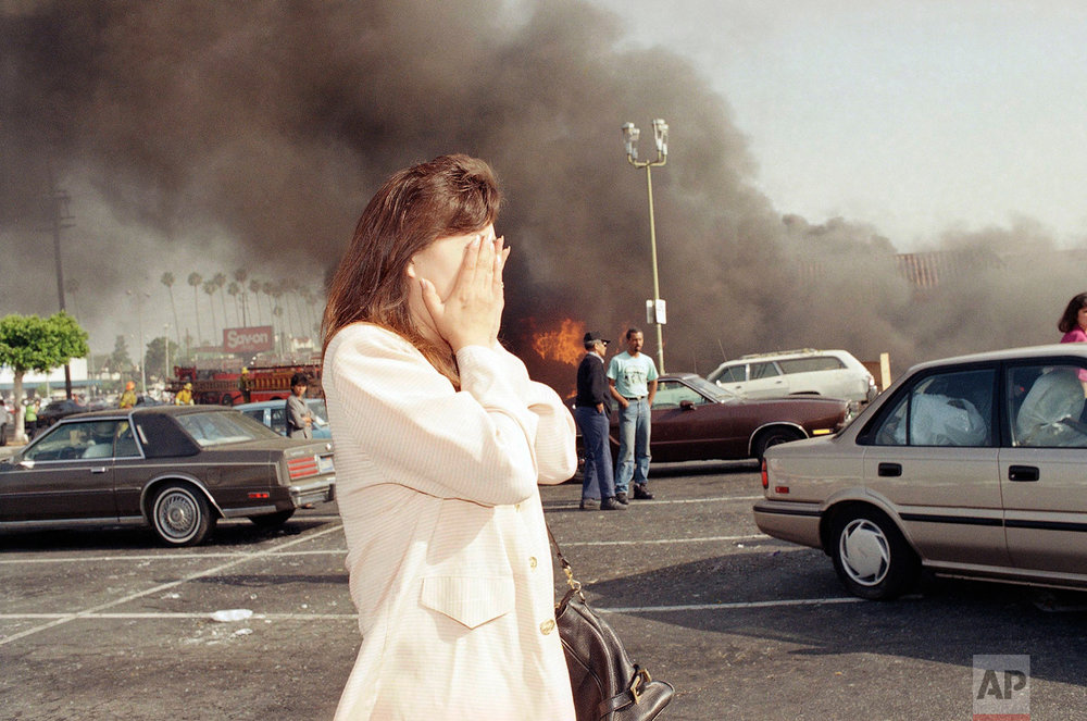 An unidentified owner of a clothing store reacts to seeing her burning business in Los Angeles, Thursday, April 30, 1992. Her store was one of more than 300 burned by rioters after the acquittal of four police officers on Wednesday in the Rodney King beating trial. (AP Photo/Nick Ut)
