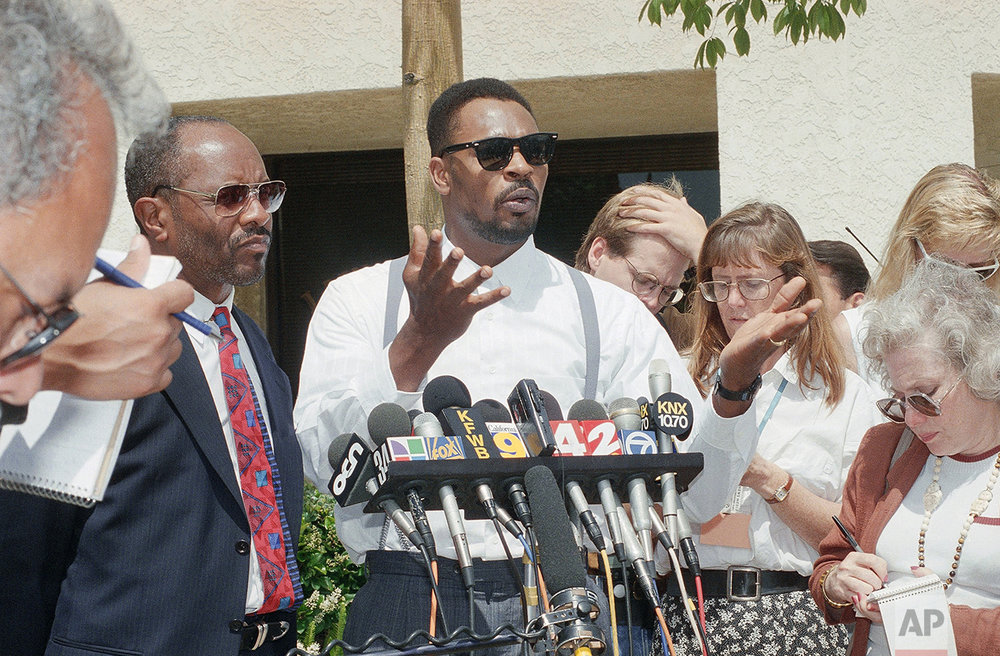 Rodney King gestures at a news conference in Santa Ana, California on Thursday, June 2, 1994 after a jury ordered on Wednesday that no punitive damages against any of the police officers involved in the March 1991 taped beating be paid. The same jury earlier ordered the city of Los Angeles to pay $3.8 million to King for his pain and suffering. Milton Grimes, King's attorney is at left. (AP Photo/Chris Martinez)