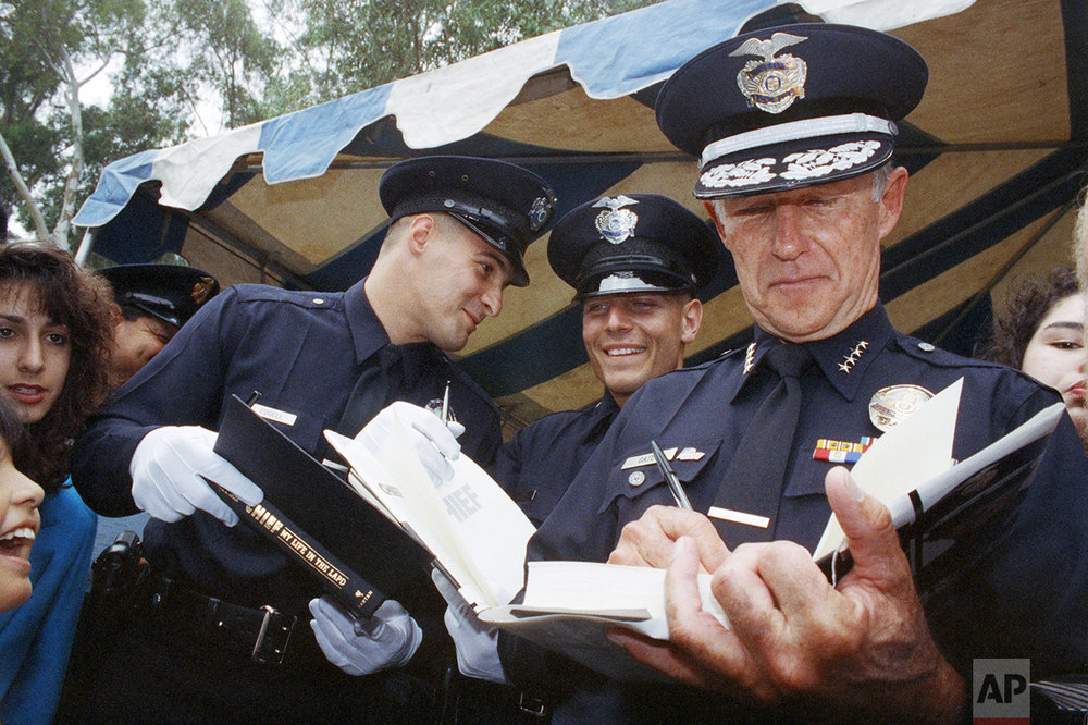 In this May 29, 1992 photo, Los Angeles Police Chief Daryl Gates autographs his book for new police officers after their graduation in Los Angeles. Police say that Gates, who resigned in the wake of 1992 rioting that followed the Rodney King beating. (AP Photo/Chris Martinez)