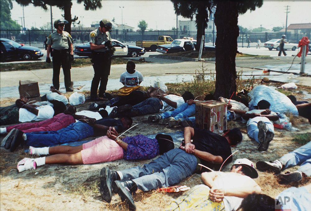 Police stand over a group of handcuffed looting suspects in Los Angeles Thursday, April 30, 1992 as rioting continued throughout the area.  The worst riots in U.S. modern history began when outnumbered police were faced down by a crowd angered by the acquittals of four white police officers accused in the videotaped beating of black motorist Rodney King.  Few lives in the city were untouched by the 1992 riots, but some were nearly destroyed.  (AP Photo/Nick Ut)