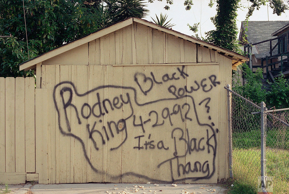 Spray-painted slogans on the wall of a small building in Los Angeles on Thursday, April 30, 1992 are indicative of the community's frustration over the acquittal of four police officers  in the Rodney King beating trial. (AP Photo/Douglas C. Pizac)