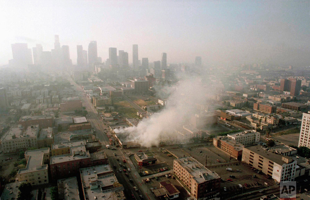 Smoke rises from a shopping center burned by rioters early Thursday morning April 30, 1992 as the Los Angeles skyline is partially obscured by smoke. More than 300 fires were reportedly set after four police officers were acquitted Wednesday of the beating of motorist Rodney King. (AP Photo/Paul Sakuma)