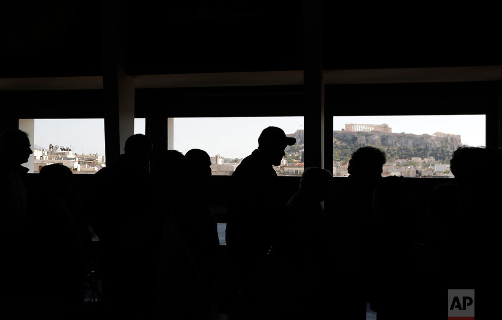 In this Tuesday, April 25, 2017 photo people stand in a queue to receive supplies from the soup kitchen ''Shelter of Love and Solidarity'' run by the Vitalaki family as the Acropolis ancient hill is seen in the background in central Athens. High unemployment and a steady decline of living standards for most Greeks for seven consecutive years have left scars on the Greek capital. (AP Photo/Thanassis Stavrakis)