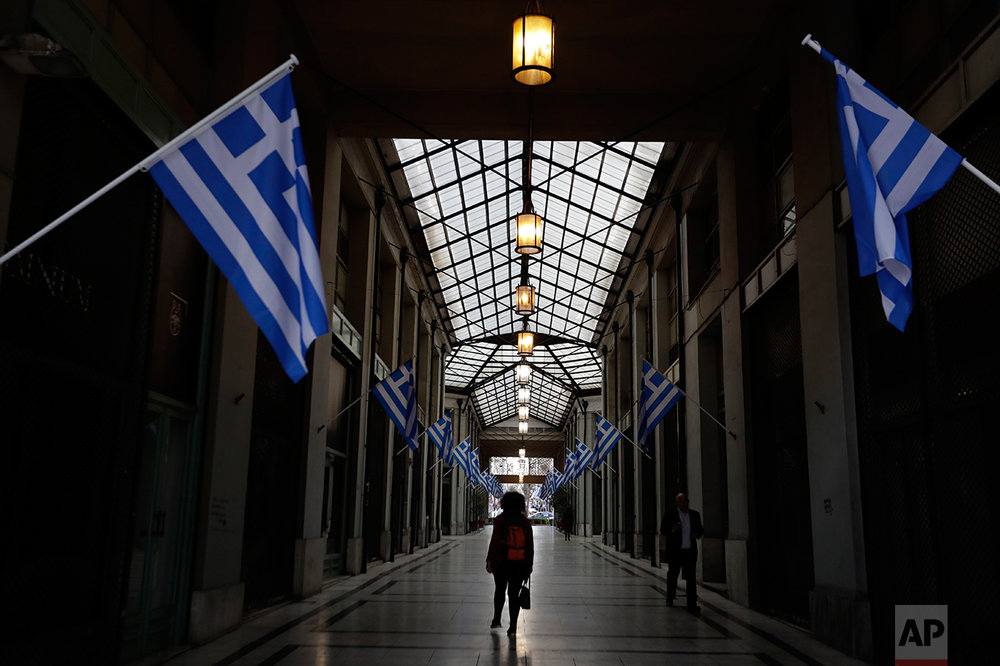 In this photo taken on Wednesday, March 22, 2017 a woman passes a shopping arcade with Greek flags, where shops closed because of the crisis in central Athens. Over the past seven years, austerity has left visible scars in Greece's capital. A walk around Athens reveals more homeless than ever despite some signs of a rosier economic outlook. Thousands of shops, mostly small businesses, are shuttered here and across the country. In what used to be a busy shopping arcade, closed stores are padlocked against a backdrop of hanging Greek flags. (AP Photo/Thanassis Stavrakis)