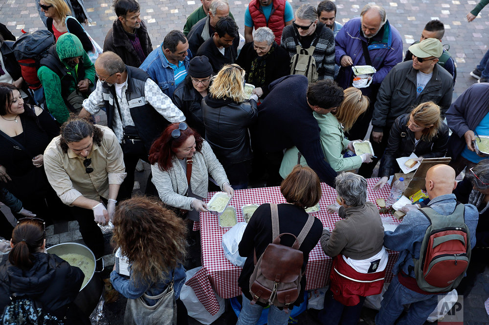 In this Tuesday, April 25, 2017 photo volunteers of soup kitchen ''O Allos Anthropos'' (The other Man) deliver free food for all at Monastiraki square in central Athens. High unemployment and a steady decline of living standards for most Greeks for seven consecutive years have left scars on the Greek capital. (AP Photo/Thanassis Stavrakis)