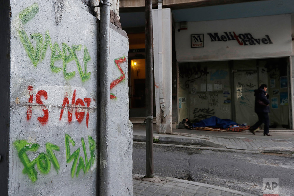 In this photo taken on Wednesday, March 22, 2017, a pedestrian passes next to a homeless person outside a closed travel agency in Athens. High unemployment and a steady decline of living standards for most Greeks for seven consecutive years have left scars on the Greek capital. (AP Photo/Thanassis Stavrakis)