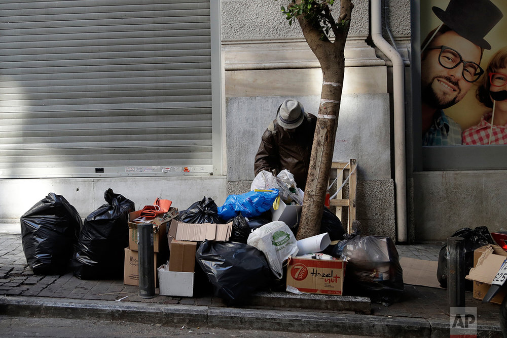 In this photo taken on Tuesday, March 28, 2017 a man searches through trash outside a store in central Athens. Over the past seven years, austerity has left visible scars in Greece's capital. A walk around Athens reveals more homeless than ever despite some signs of a rosier economic outlook. Thousands of shops, mostly small businesses, are shuttered here and across the country. In what used to be a busy shopping arcade, closed stores are padlocked against a backdrop of hanging Greek flags. (AP Photo/Thanassis Stavrakis)