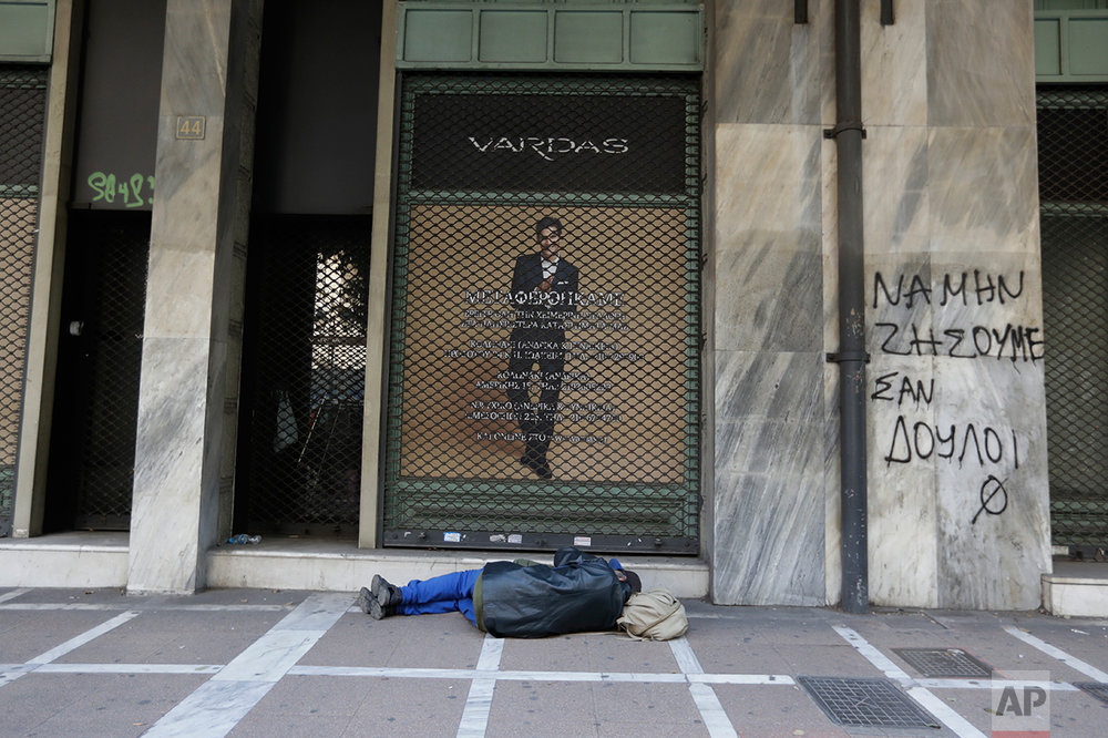 In this photo taken on Tuesday, March 21, 2017 a homeless person sleeps on the pavement outside a closed shop as the graffiti reads ''Do not live like slaves'' in central Athens. High unemployment and a steady decline of living standards for most Greeks for seven consecutive years have left scars on the Greek capital. (AP Photo/Thanassis Stavrakis)