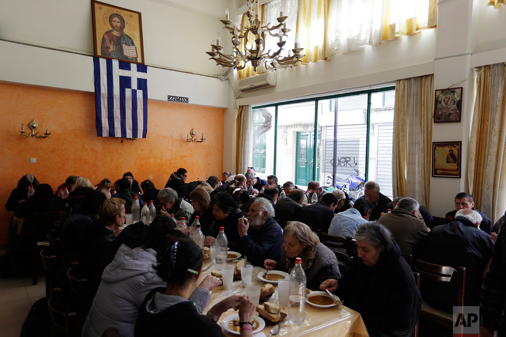 "In this photo taken on Wednesday, March 29, 2017, homeless persons eat lunch at a soup kitchen run by the Church of Greece in Athens. ""Every day we feed 400 to 500 people, and this number has increased even more in the past two years,"" says Evangelia Konsta, organizer and sponsor of the meals offered by the Church of Greece in a run-down neighborhood in central Athens. (AP Photo/Thanassis Stavrakis)"