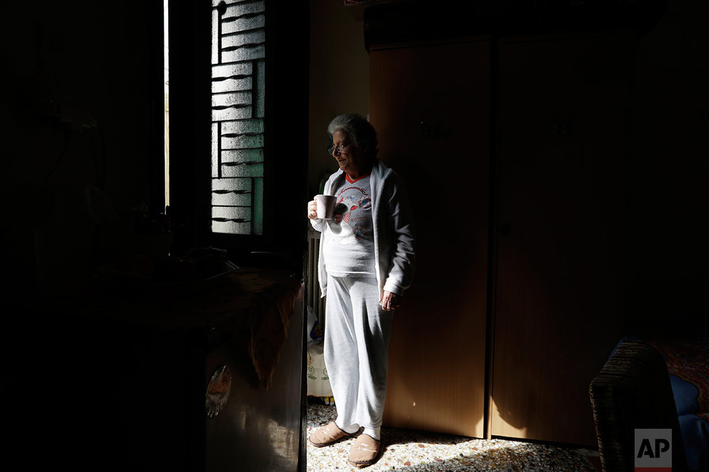 In this photo taken on Tuesday, April 4, 2017, cancer patient Angeliki Garoufalia, a 62-year-old retired nurse, stands at the door of her room of a homeless shelter run by the Church of Greece, in Athens. High unemployment and a steady decline of living standards for most Greeks for seven consecutive years have left scars on the Greek capital. (AP Photo/Thanassis Stavrakis)
