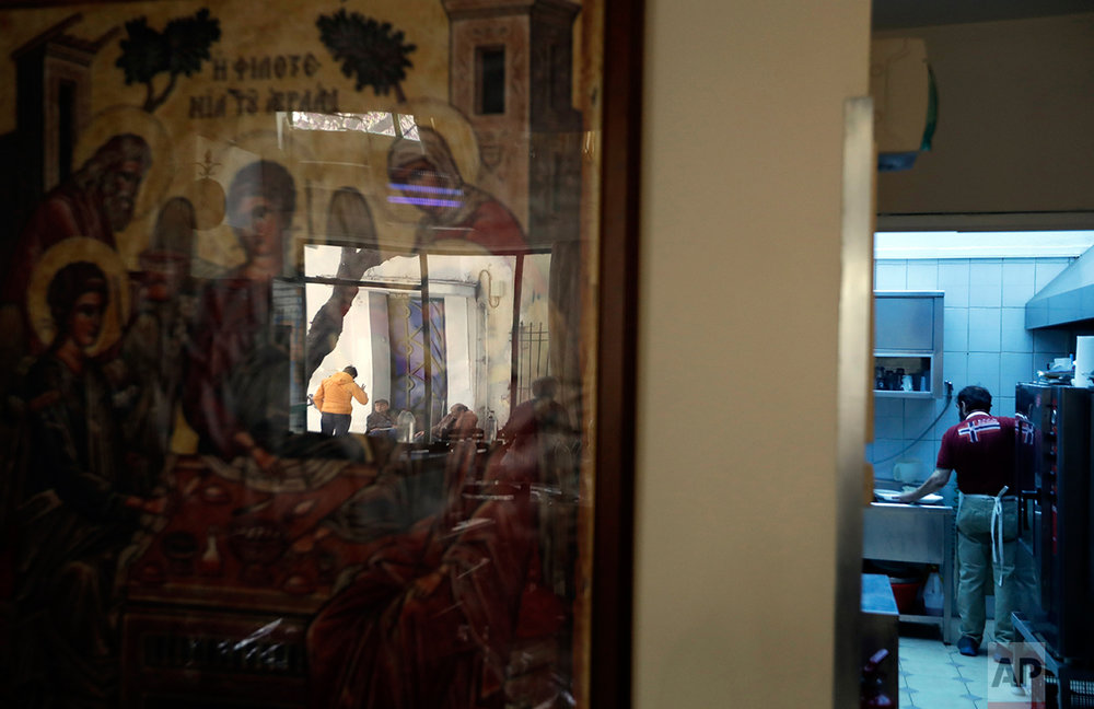 "In this photo taken on Wednesday, March 29, 2017, homeless persons are reflected in a religious icon as a volunteer cooks at a soup kitchen run by the Church of Greece in Athens. ""Every day we feed 400 to 500 people, and this number has increased even more in the past two years,"" says Evangelia Konsta, organizer and sponsor of the meals offered by the Church of Greece in a run-down neighborhood in central Athens. (AP Photo/Thanassis Stavrakis)"