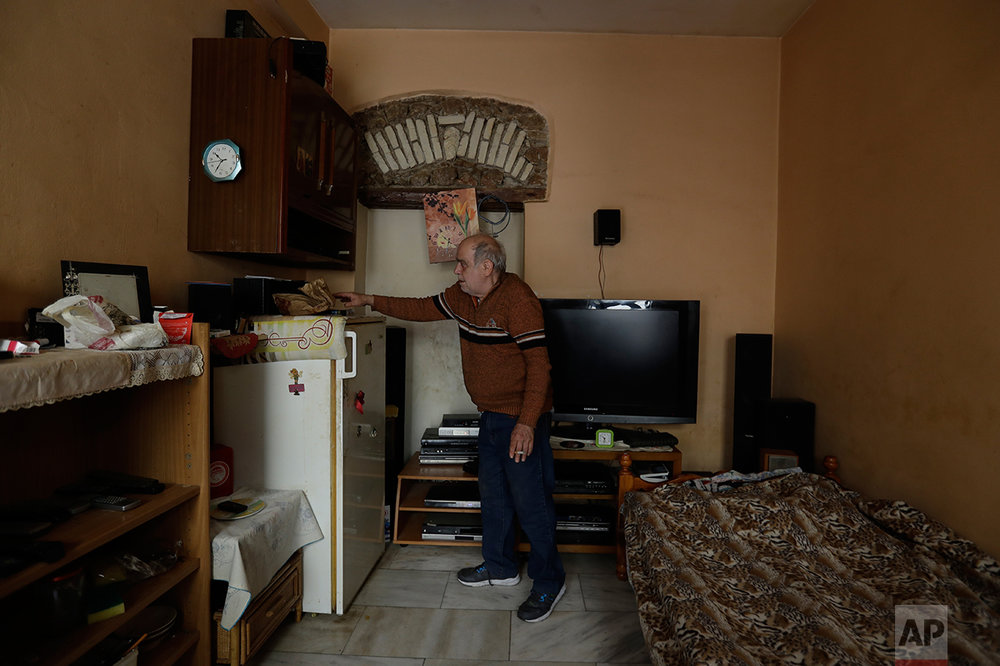 In this photo taken on Tuesday, April 4, 2017, former seaman Giorgos Farmakioris, a 59-year-old, stands at his room of a homeless shelter run by the Church of Greece , in Athens. A walk around Athens reveals more homeless than ever despite some signs of a rosier economic outlook. Thousands of shops, mostly small businesses, are shuttered here and across the country. In what used to be a busy shopping arcade, closed stores are padlocked against a backdrop of hanging Greek flags. (AP Photo/Thanassis Stavrakis)