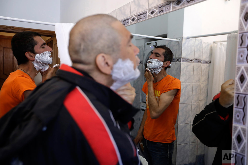In this Tuesday, April 25, 2017 photo homeless persons Dimitris, right, and Ilias Kozakis shave at ''Shelter of Love and Solidarity'' run by the Vitalaki family in central Athens. High unemployment and a steady decline of living standards for most Greeks for seven consecutive years have left scars on the Greek capital. (AP Photo/Thanassis Stavrakis)