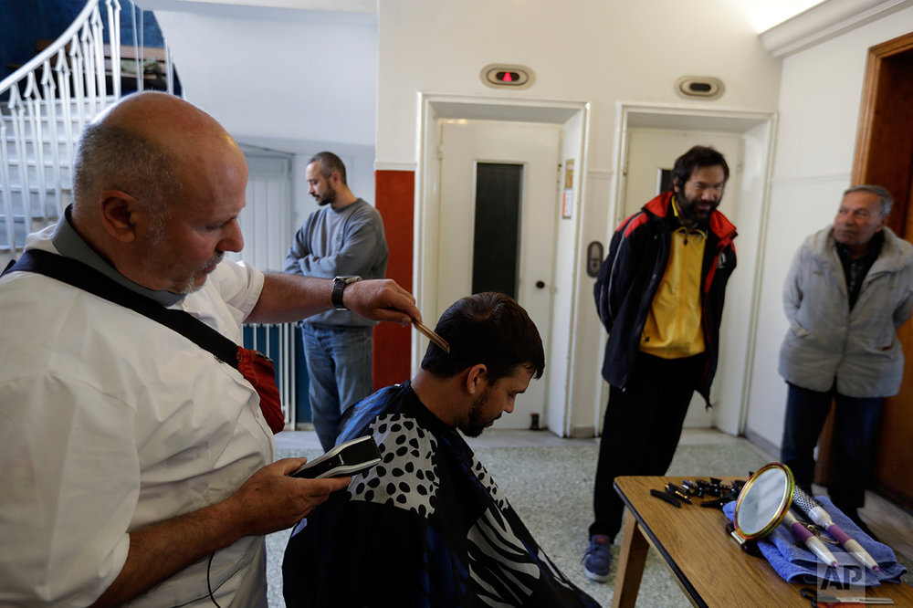 In this Tuesday, April 25, 2017 photo a barber cuts the hair of a volunteer as homeless persons wait outside the ''Shelter of Love and Solidarity'' run by the Vitalaki family in central Athens. High unemployment and a steady decline of living standards for most Greeks for seven consecutive years have left scars on the Greek capital. (AP Photo/Thanassis Stavrakis)