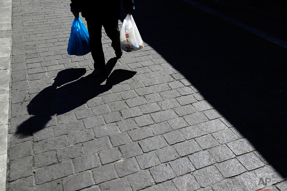 In this photo taken on Tuesday, March 28, 2017, an elderly man carries shopping bags at Varvakios market in Athens. Over the past seven years, austerity has left visible scars in Greece's capital. A walk around Athens reveals more homeless than ever despite some signs of a rosier economic outlook. Thousands of shops, mostly small businesses, are shuttered here and across the country. In what used to be a busy shopping arcade, closed stores are padlocked against a backdrop of hanging Greek flags. (AP Photo/Thanassis Stavrakis)