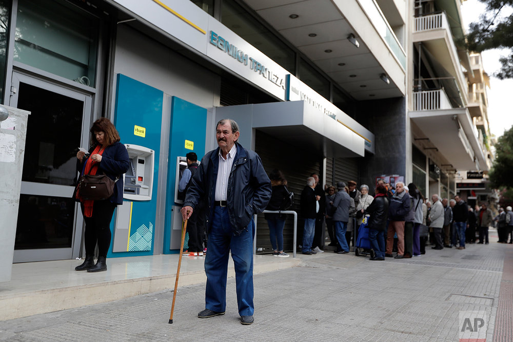 In this photo taken on Tuesday, April 4, 2017, retirees wait for a bank branch to open to receive their monthly pension payments. High unemployment and a steady decline of living standards for most Greeks for seven consecutive years have left scars on the Greek capital. (AP Photo/Thanassis Stavrakis)