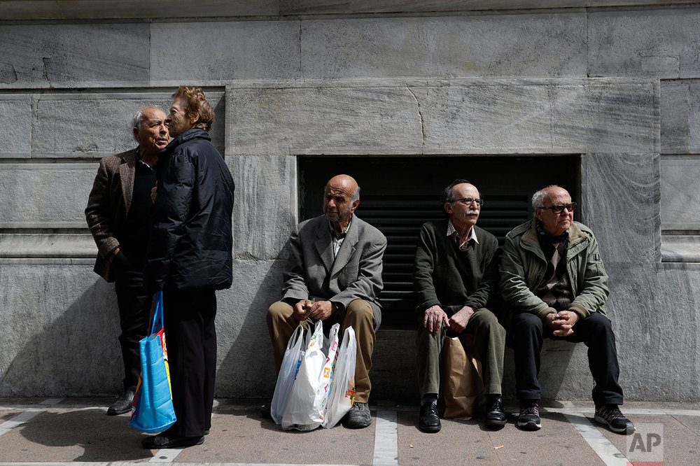 In this photo taken on Tuesday, April 4, 2017 pensioners take part in protest outside Labor ministry in central Athens. Over the past seven years, austerity has left visible scars in Greece's capital. A walk around Athens reveals more homeless than ever despite some signs of a rosier economic outlook. Thousands of shops, mostly small businesses, are shuttered here and across the country. In what used to be a busy shopping arcade, closed stores are padlocked against a backdrop of hanging Greek flags. (AP Photo/Thanassis Stavrakis)
