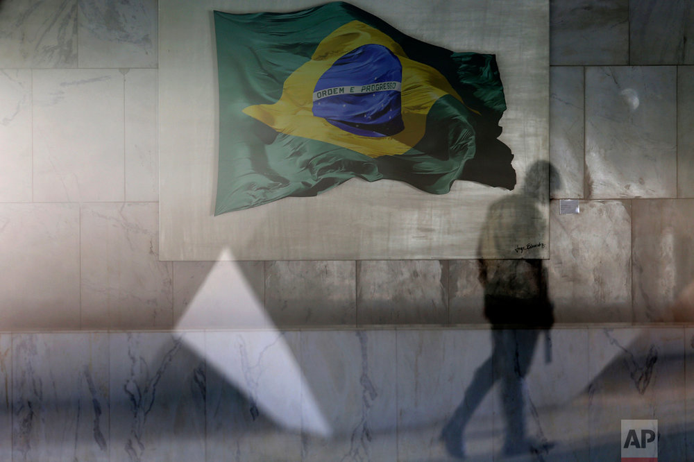 A presidential guard walks past a window that allows a view into the Planalto presidential palace's main lounge, decorated with an image of a Brazilian national flag, in Brasilia, Brazil, Thursday, April 13, 2017. Brazilian construction giant Odebrecht paid millions in bribes to President Michel Temer's party and another party, to ensure a contract with the state oil company, according to plea bargain testimony from a former executive at the company, released Wednesday, as part of the biggest corruption probe in Brazil's history. (AP Photo/Eraldo Peres)