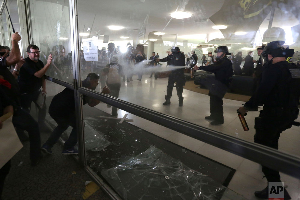 Police officers attempt to break into the Brazilian National Congress during a protest by police officers from several Brazilian states against pension reforms proposed by Brazil's President Michel Temer's government that would end the special pension retirement of police officers, in Brasilia, Brazil, Tuesday, April 18, 2017. (AP Photo/Eraldo Peres)