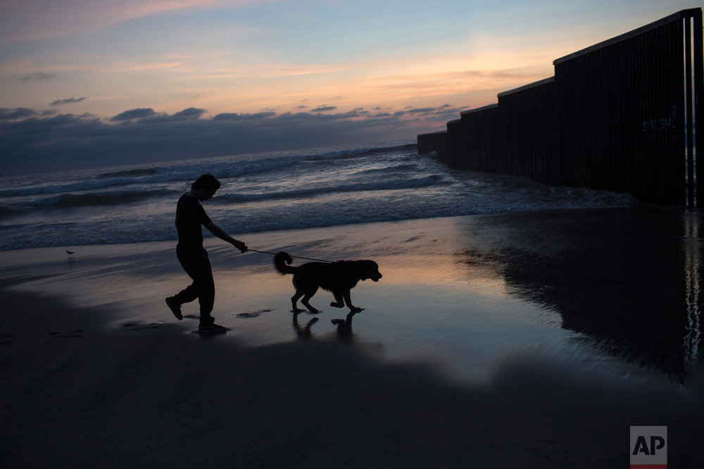 A man and his dog are silhouetted against an early evening landscape while walking along a Pacific Ocean shore, near the U.S. border fence that separates Tijuana, Mexico from San Diego, Calif., Tuesday, April 4, 2017. (AP Photo/Rodrigo Abd)