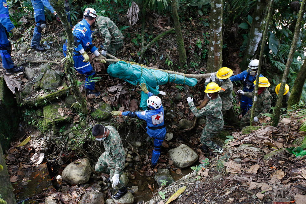 Soldiers and members of the Colombian Red Cross recover the body of a victim of a deadly avalanche that happened following heavy rains, in Mocoa, Colombia, Monday, April 3, 2017. The grim search continues for the missing in southern Colombia after surging rivers sent an avalanche of floodwaters, mud and debris through the small city, killing more than 260 people and leaving many more injured and homeless. (AP Photo/Fernando Vergara)
