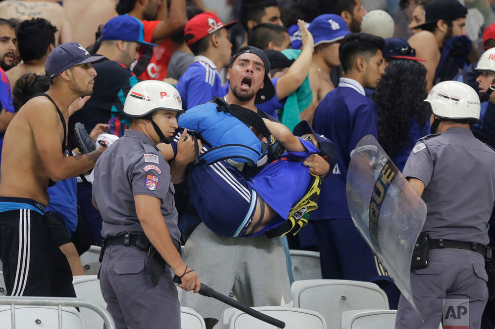 A fan of Universidad de Chile carries a mate that collapsed when they clashed with the police during a Copa Sudamericana soccer match against Brazil's Corinthians in Sao Paulo, Brazil, Wednesday, April 5, 2017. (AP Photo/Nelson Antoine)