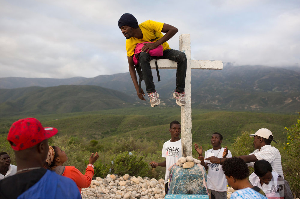 Haitians gather at the 14th station of the cross around a man sitting on the horizontal bar of the cross, who they believe has been taken over by a voodoo spirit, during the annual Good Friday pilgrimage to the mount Calvaire Miracle, in Ganthier, Haiti, Friday, April 14, 2017. (AP Photo/Dieu Nalio Chery)