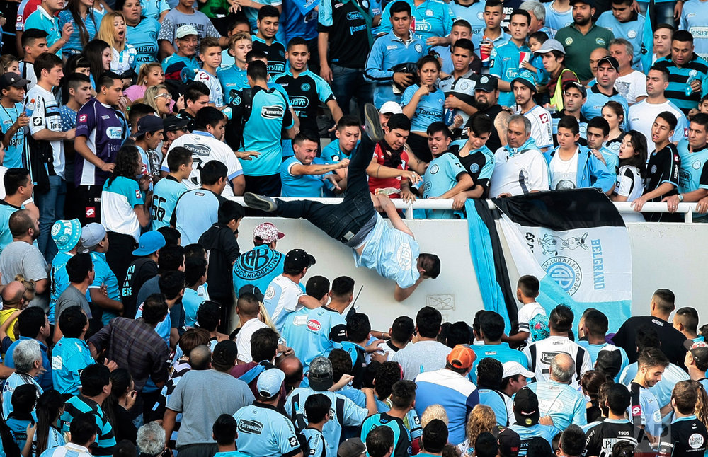 In this Saturday, April 15, 2017 photo, Emanuel Balbo is thrown from the stands by other fans during a match between Belgrano and Talleres, in Cordoba, Argentina. Balbo has been declared brain dead after he was chased down the terraces of a stadium and thrown from the bleachers. Balbo's father says his son was attacked by a mob after he faced off with a man that Balbo blamed for killing his brother. (AP Photo/Alvaro Martin Corral)
