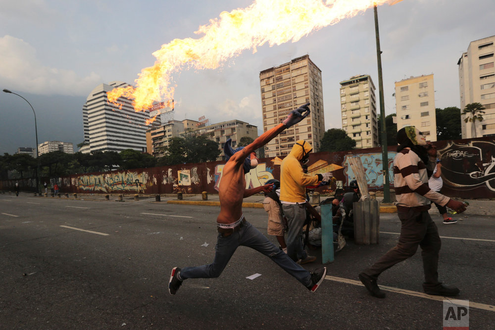 "An anti-government protesters throws a molotov bomb at security forces in Caracas, Venezuela, Wednesday, April 19, 2017. Tens of thousands of opponents of President Nicolas Maduro flooded the streets of Caracas in what's been dubbed the ""mother of all marches"" against the embattled socialist president. (AP Photo/Fernando Llano)"